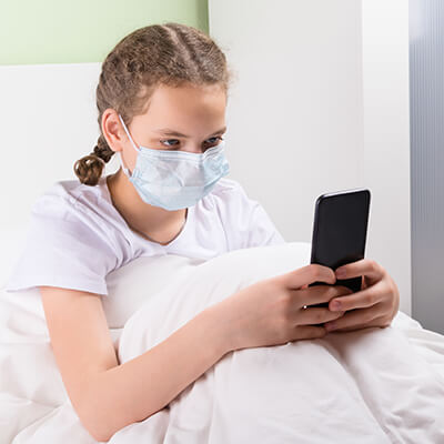 picture of girl sitting in bed sick and playing in phone